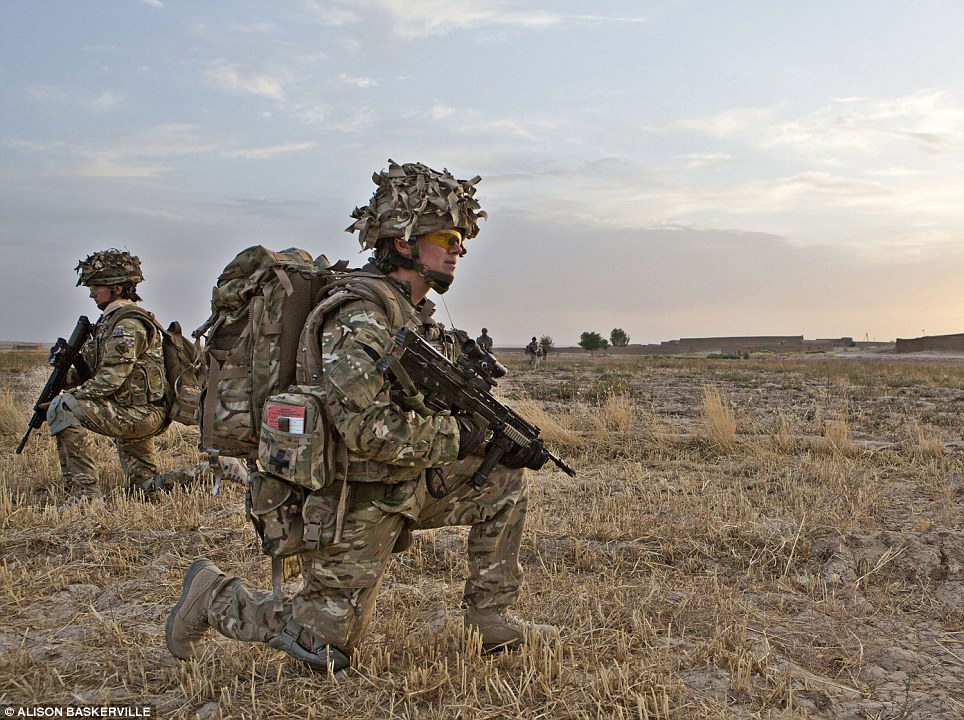 Expectant: Captain Crossley is pictured in the Upper Gereshk Valley of Helmand.  Here she kneels down as she joins a patrol to see whether she can access a local Afghan compund in the hope that she may meet women and children