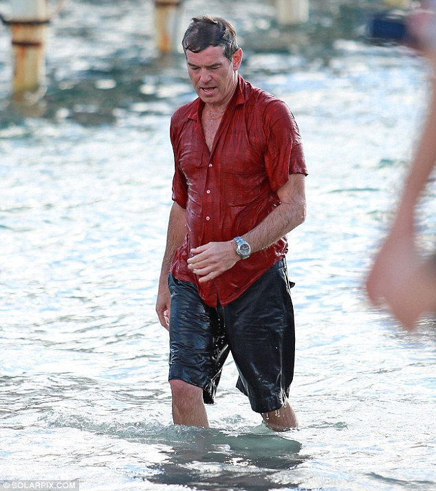 Heading back in: Brosnan looked serious once more as he got back out of character and the cameras stopped rolling