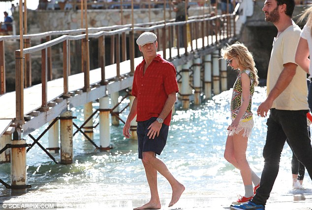 Dried off: Pierce wore a flat cap as he later took a stroll around the shore covering himself up from the sun