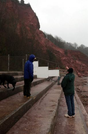 Onlookers survey the 5,000 tons of rubble which fell away from the cliff by the six-bedroom property overlooking Oddicombe Beach in Torquay, Devon