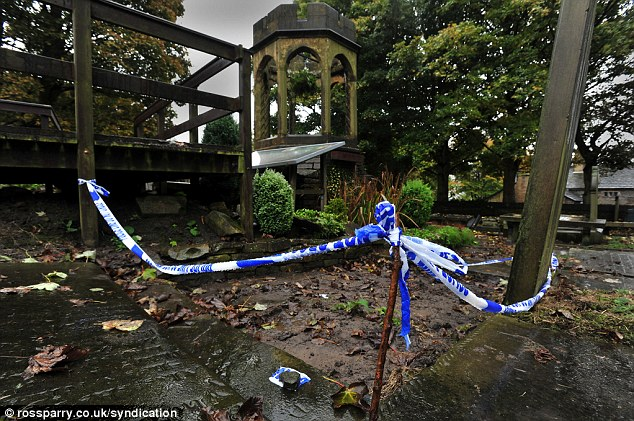 Desecrated: Bare earth is exposed where thieves tore up a Yorkshire Stone burial slab outside by the old bell chapel in Thornton, West Yorkshire
