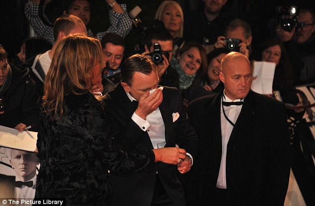 Bit much? Daniel Craig had to take a moment out from posing for cameras as he grabbed a tissue
