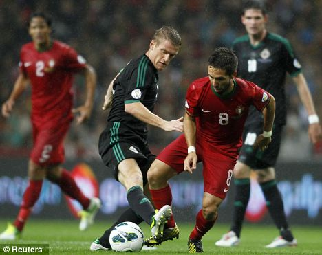 Portugal's Joao Moutinho (front R) battles for the ball with Northern Ireland's Steven Davis