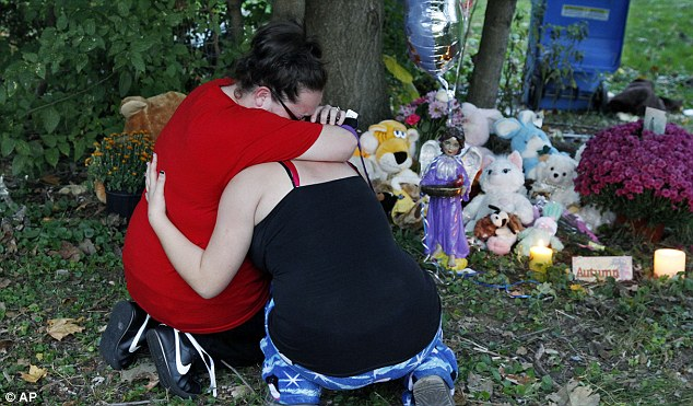 Mourning: Sisters Alexis and Bethany Davis, left, cry at a shrine for Autumn Pasquale yesterday not far from where her body was found