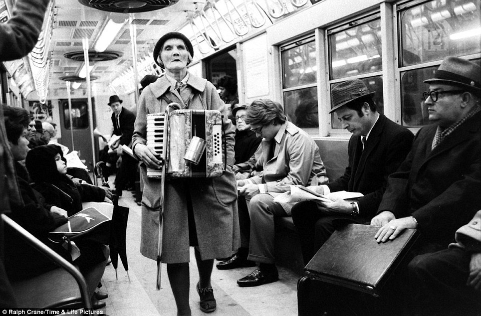 In-car entertainment: An elderly woman buskers with a cane and accordion on the subway in 1969, though the riders don't seem too moved by the performance