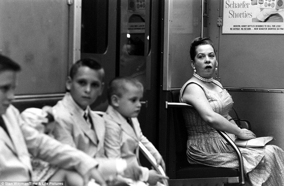 In transit: A woman with a pearl necklace and earrings looks over at a group of young boys, pictured in 1959