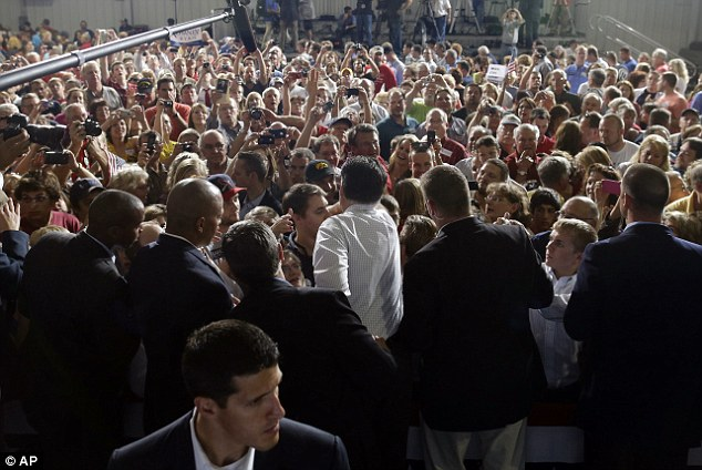 Crowds: Mitt Romney, center, is surrounded by supporters at The Eastern Iowa Airport in Cedar Rapids, Iowa, yesterday