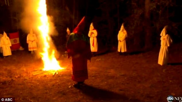 Members of the Mississippi Klan engage in the burning of a giant cross