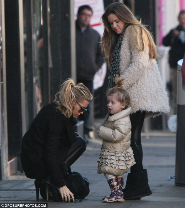 Drop dead gorgeous: Abbey crouches down to the ground as she takes her daughter shopping in Liverpool on Saturday