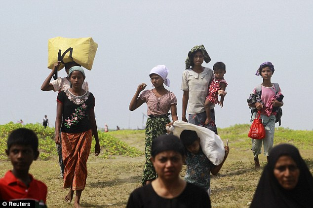 Displaced: People moving after the recent violence in the Kyukphyu township carry their belongings