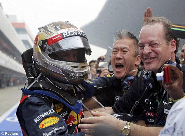 Team work: Vettel is congratulated by members of the Red Bull crew after his convincing victory