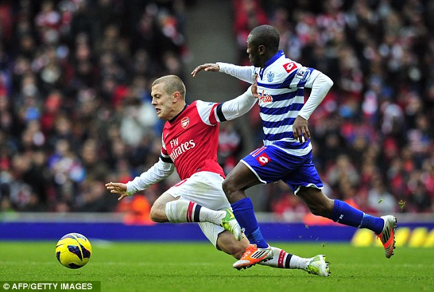 Getting stuck in: Wilshere vies with Shaun Wright-Phillips during Arsenal's win over QPR