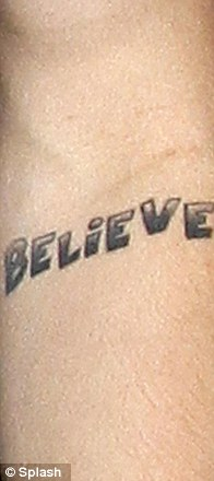 Inked: The singer also has a 'Believe' tattoo on his forearm, the Japanese Kanji symbol for music on his right arm and an image of Jesus etched onto his left leg