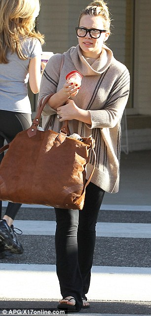That's one big bag: Hilary practically covered herself with her tote; which also provided room for all the containers that go with a baby