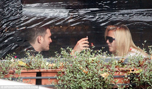 Happy meal: The pair share a joke from something on Buble's phone