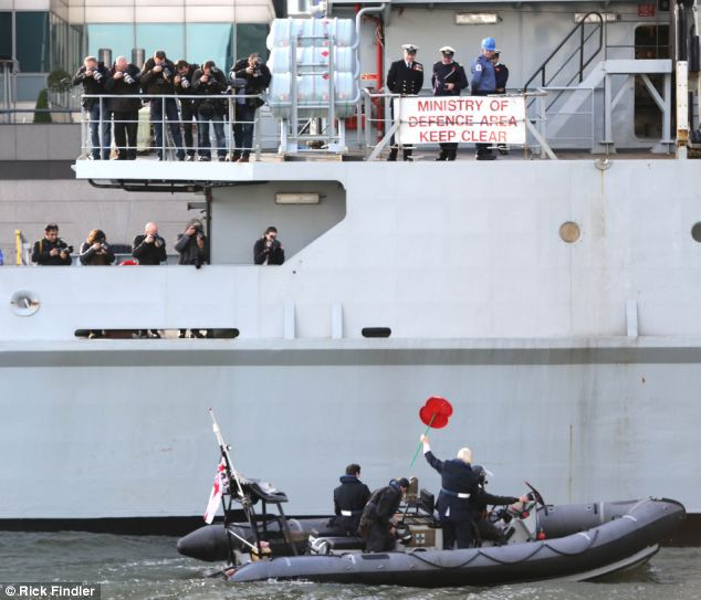 After pulling alongside HMS Severn, Mr Johnson held large poppy aloft before boarding the warship at South Quay, London
