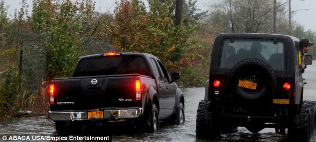 The Staten Island shoreline was flooded as superstorm Sandy struck the American east coast - these motorists can go no further because of the flood water