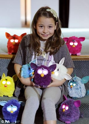 A child poses with Furby toys at theToy Retailers Association's Dream Toys exhibition