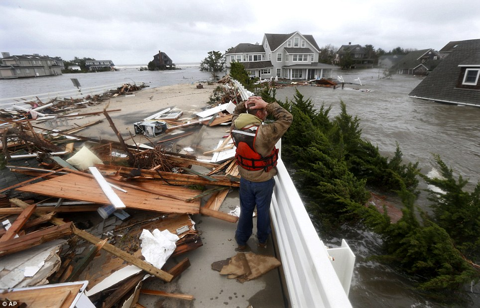 Shock: Brian Hajeski, 41, of Brick, New Jersey, reacts as he looks at debris of a home that washed up on to the Mantoloking Bridge the morning after Superstorm Sandy