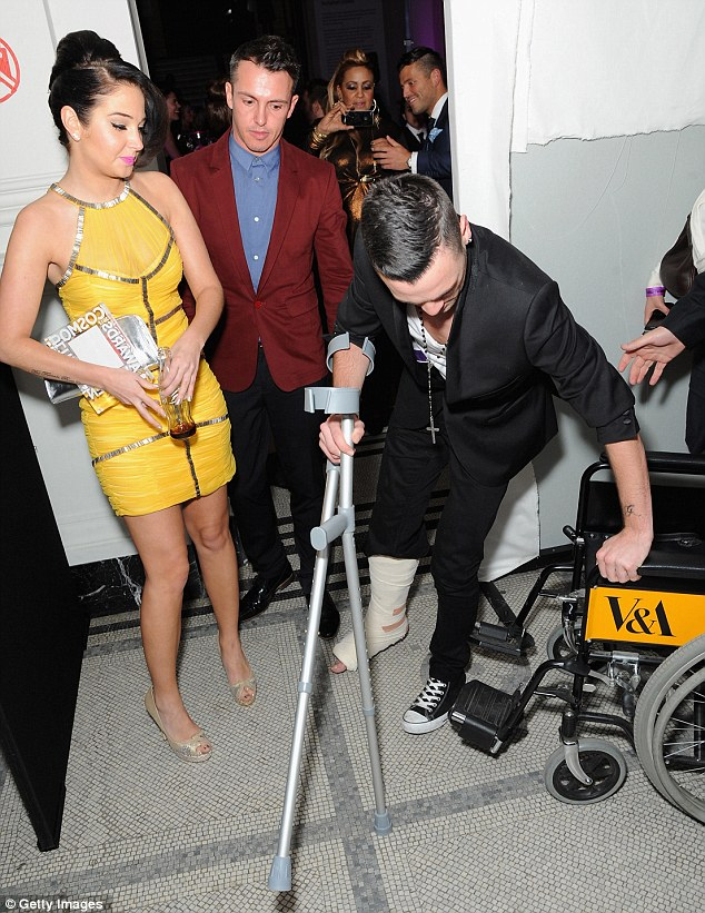 Take a load off: Tulisa watched on as her personal assistant Gareth Varey hobbled into his wheelchair