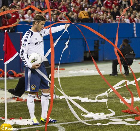 MLS fans cover David Beckham as he is about to take a corner against Toronto
