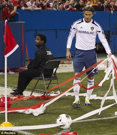 Stream on: Beckham looks to be searching for the ball in Toronto their fans shower him with streamers