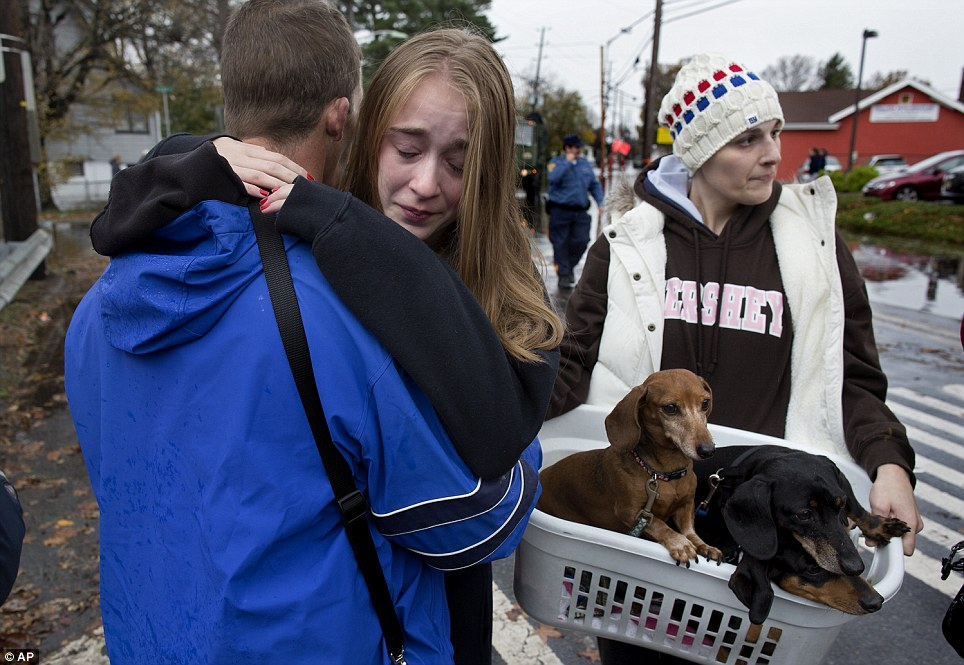 Pet rescue: Olivia Loesner, 16, hugs her uncle, Deputy Fire Chief John Ruff, after she was brought from her flooded home in a boat in Little Ferry, New Jersey, Her mother, Janice Loesner, carries their dogs to safety in a basket