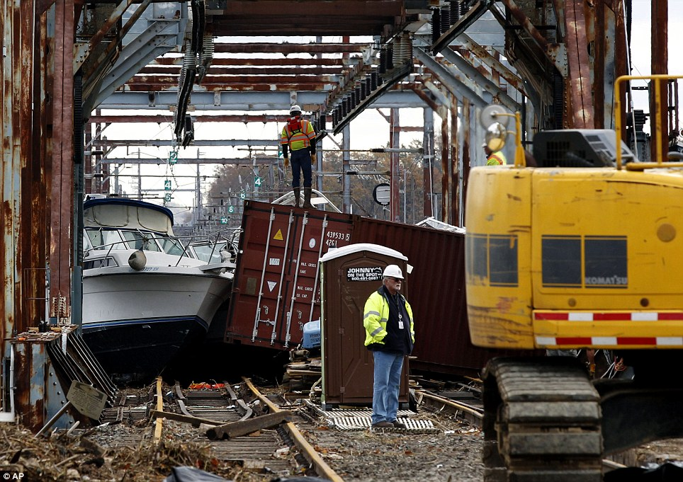 Huge task: Workers try to clear boats and debris from the New Jersey Transit Morgan draw bridge in South Amboy, New Jersey, after the storm surge pushed them on to the train tracks