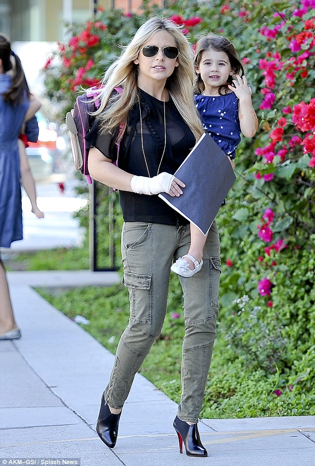 Doting mother: Sarah schedules her day around her daughter. Here she's pictured on October 19 carrying Charlotte and her daughter's rucksack and homework, all with a bandaged wrist