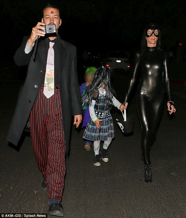 United front: Rupert Sanders - who Stewart was caught kissing earlier this year, made more of an effort with his outfit while out trick or treating with his children and wife Liberty Ross, who was wearing a catsuit