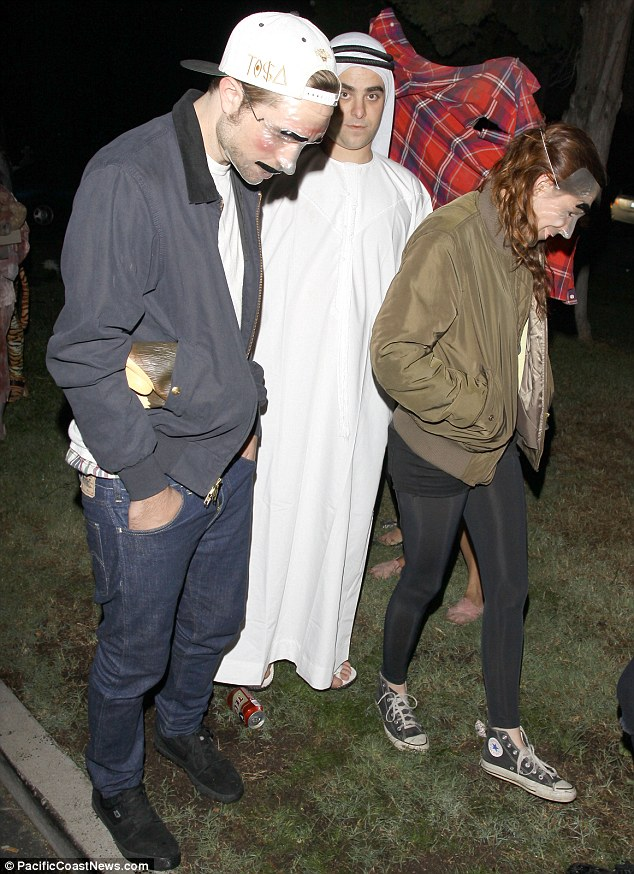 Not all that spooky: The pair donned see-through plastic masks at the Hollywood Forever Cemetery in LA