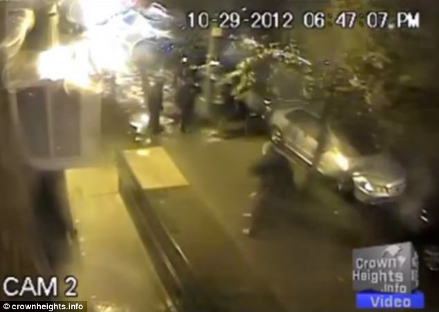 Threat: The video shows four of the robbers casually walking away as a fifth lingers. He puts his foot on Mr Furchtgott's head, pushing his face into the sidewalk, and says: 'Stay down! Don't look up until you count to 100 or I'll shoot you!'