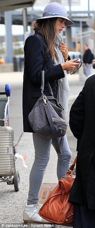 Chic flying attire: Wearing a pair grey leggings, a navy brocade blazer and some Isabel Marant high-top sneakers, she hightailed it into the limousine