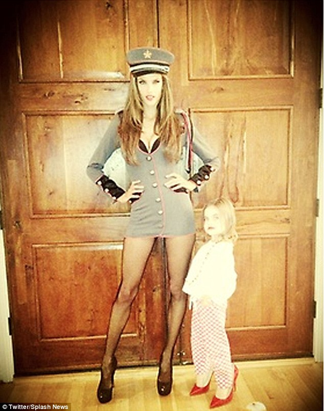 Strike a pose: Alessandra's daughter wore a pair of her mother's heels as she posed with the supermodel last week before Alessandra went to an grown-ups Halloween party