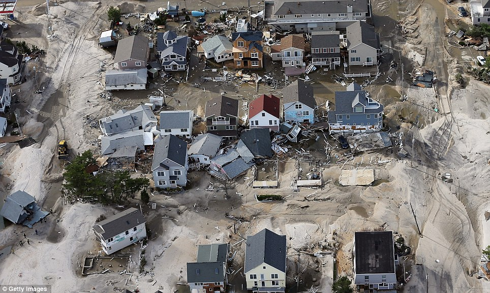 Homes devastated: Homes wrecked by Superstorm Sandy sit amongst sand washed ashore in Seaside Heights