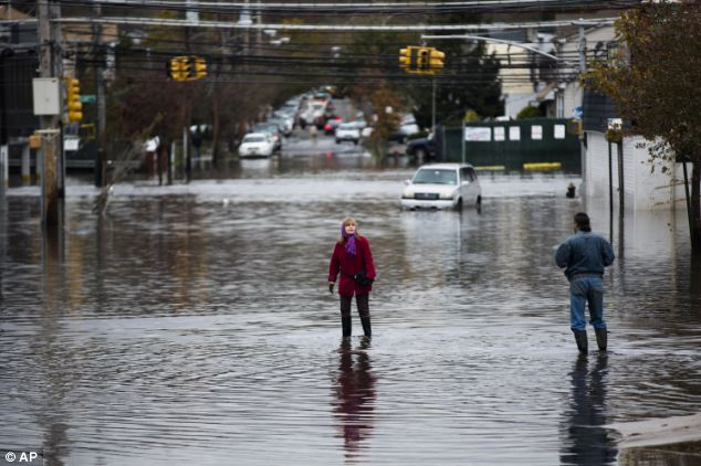 Needing help: A woman stands in a street flooded by Superstorm Sandy in Staten Island
