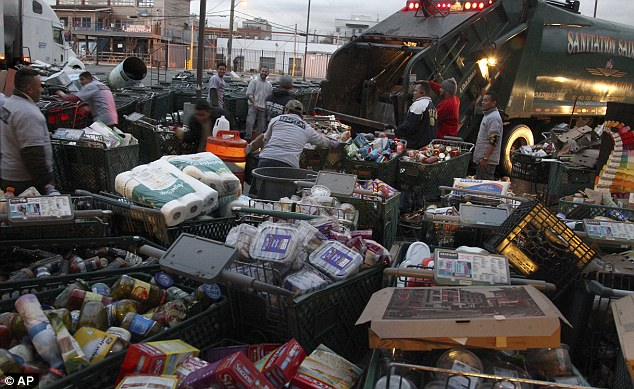 Hauled away: Garbage men disposed dozens of shopping carts full of ruined goods on Wednesday at the Fairway supermarket in Red Hook, Brooklyn, New York