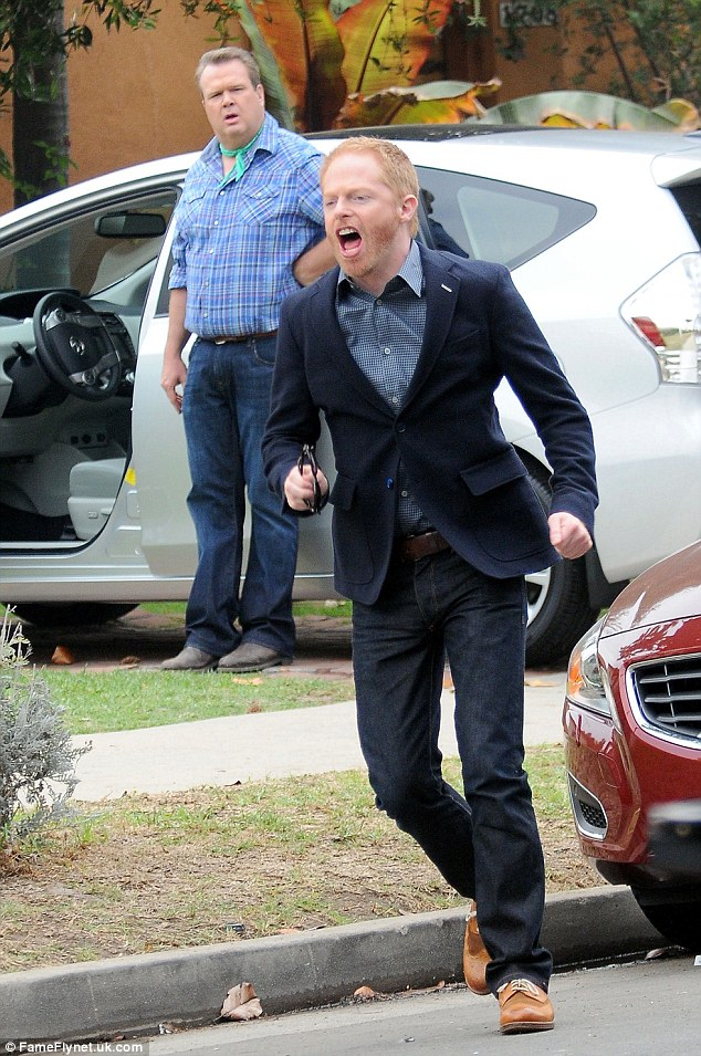 Watch out for traffic: Jesse Tyler Ferguson is seen running in character - and into the street - while filming a scene for the hit ABC show