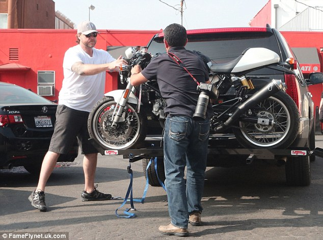 Dropping off the bike: A photographer helped Dean unstrap his bike from the back of his SUV