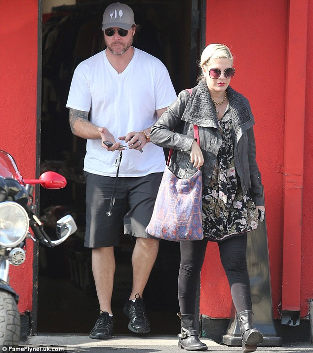 Biker chic: Tori Spelling sports a chunky leather jacket and boots as she joins husband Dean McDermott to drop off his motorcycle at a repair shop on Friday