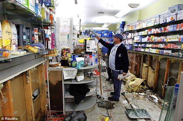 Postman Mike Conroy delivers the mail to a pharmacy damaged by floodwaters as postal services resume in Hoboken, New Jersey