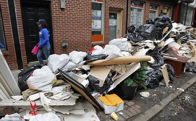 Still a long way to go: A woman walks past debris piled in the streets of Hoboken, New Jersey