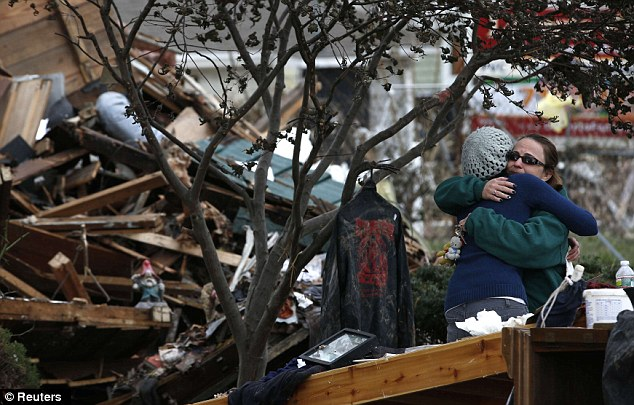 Everything lost: Two women embrace outside a home destroyed by flooding on the south side of Staten Island