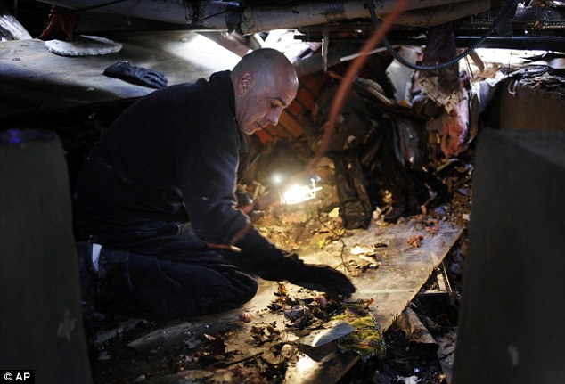 Gathering belongings: Christopher Traina tries to salvage some personal items from the basement of his parent's Staten Island home, which was destroyed