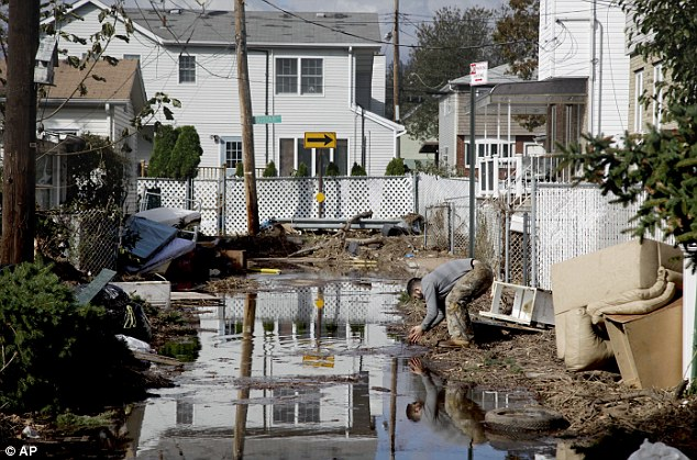 Poor sanitation: A man rinses his hands in flood water while cleaning out a house in a hard-hit neighbor hood in Staten Island