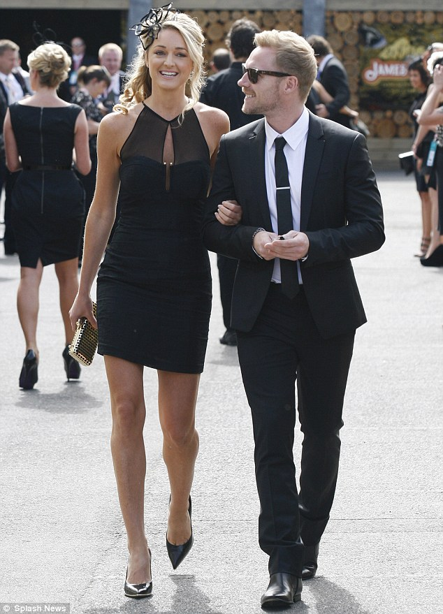 The look of love: Ronan looked positively smitten with his stunning lady as the couple soaked up the sun while wandering around the racecourse