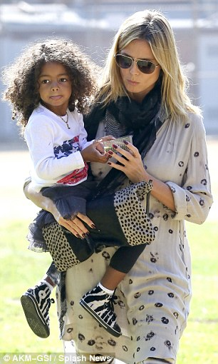 Doting: As the family headed back to the car, doting mother Heidi scooped little Lou up into her arms as the youngster snacked on a healthy treat