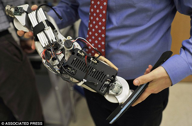 Futuristic: Dr. Levi Hargrove, lead researcher for the Rehabilitation Institute of Chicago's Center for Bionic Medicine, holds an experimental 'bionic' prosthetic leg at the institute