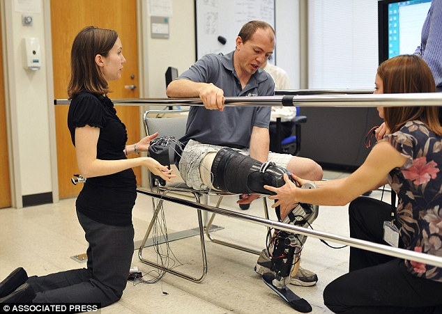 Practice makes perfect: Biomedical engineer Annie Simon, left, and research prosthetist Elizabeth Halsne fit an experimental leg on Zac Vawter during days of practice