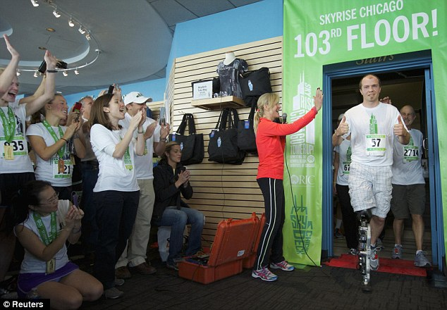 Mind blowing: Zac Vawter celebrates climbing to the top of the 103-story Willis Tower using the worlds first neural-controlled Bionic leg in Chicago